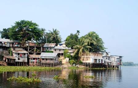 Encroachment of wetlands often starts with huts built on bamboo stilts