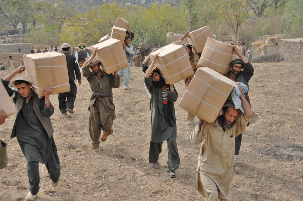 Afghan men from the Wagel valley carry boxes full of humanitarian aid during a handout in the Dudarek village in Afghanistan. The aid included blankets, pots and pans, and women's clothing
