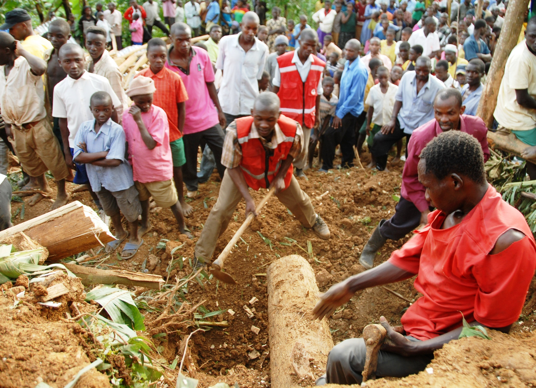 The local and Uganda Red Cross Society rescue teams trying to search for any survivors of the 25 June 2012 landslide that buried over 100 people including school children according to government and local officials