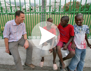 Robert Schofield with some local children in front of the collapsed Haiti presidential palace