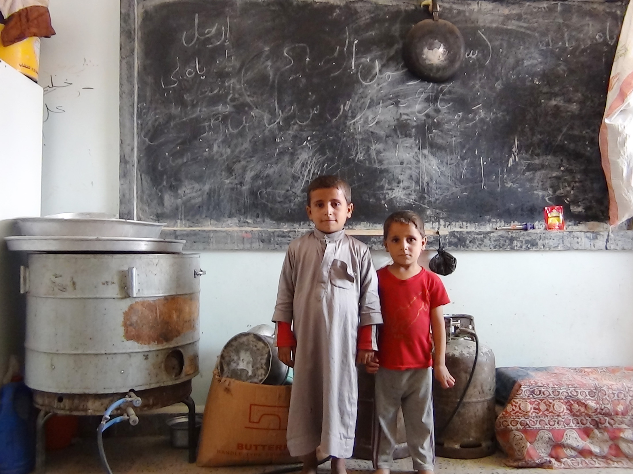 Child IDPs with their family belongings in an Aden classroom