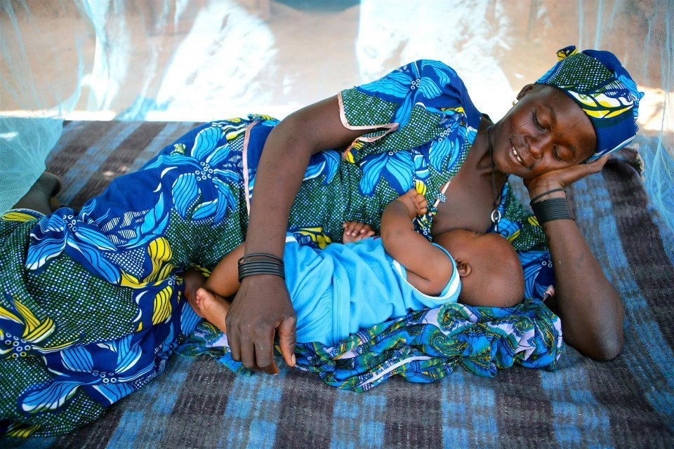 A woman breastfeeds her baby under a mosquito net in Garin Badjini village, Niger