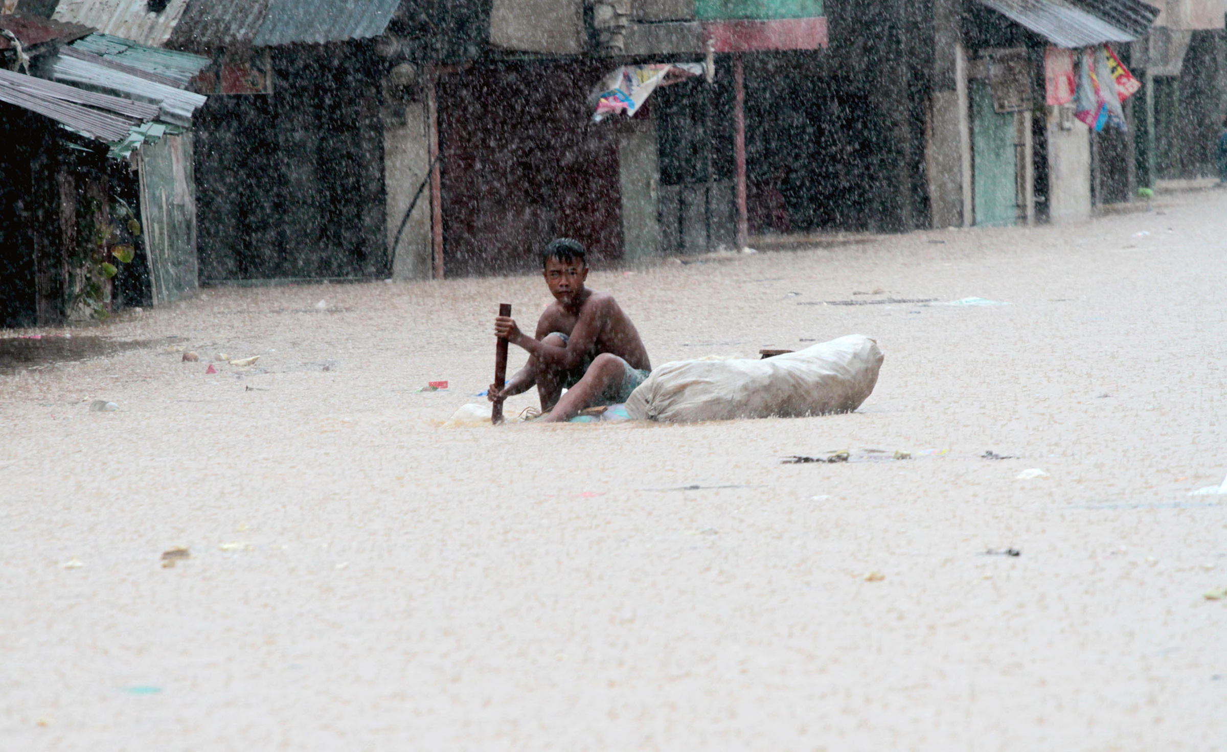 A boy on an improvised raft travels down a flooded road in a slum district of Tumana, near Marikina, in the Philippines (Aug 2012)