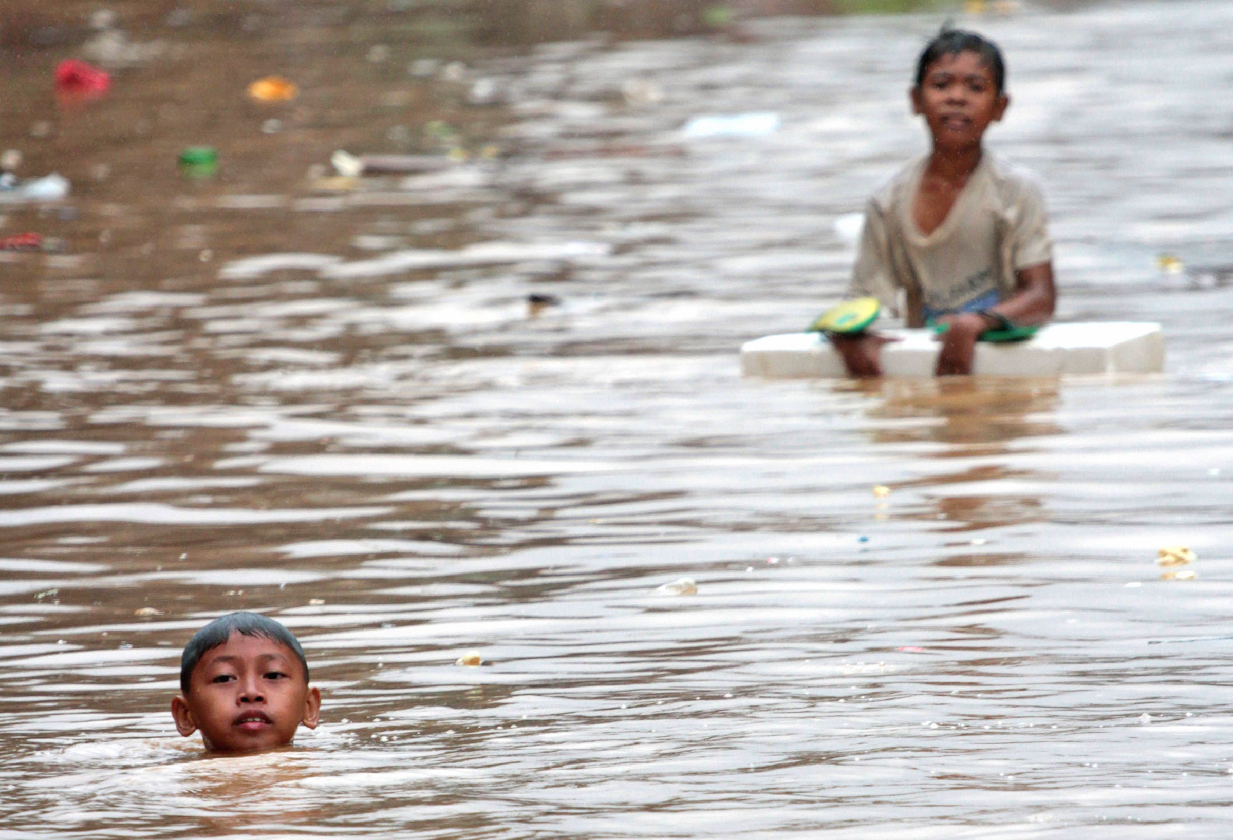 Boys wade in floodwaters in Manila