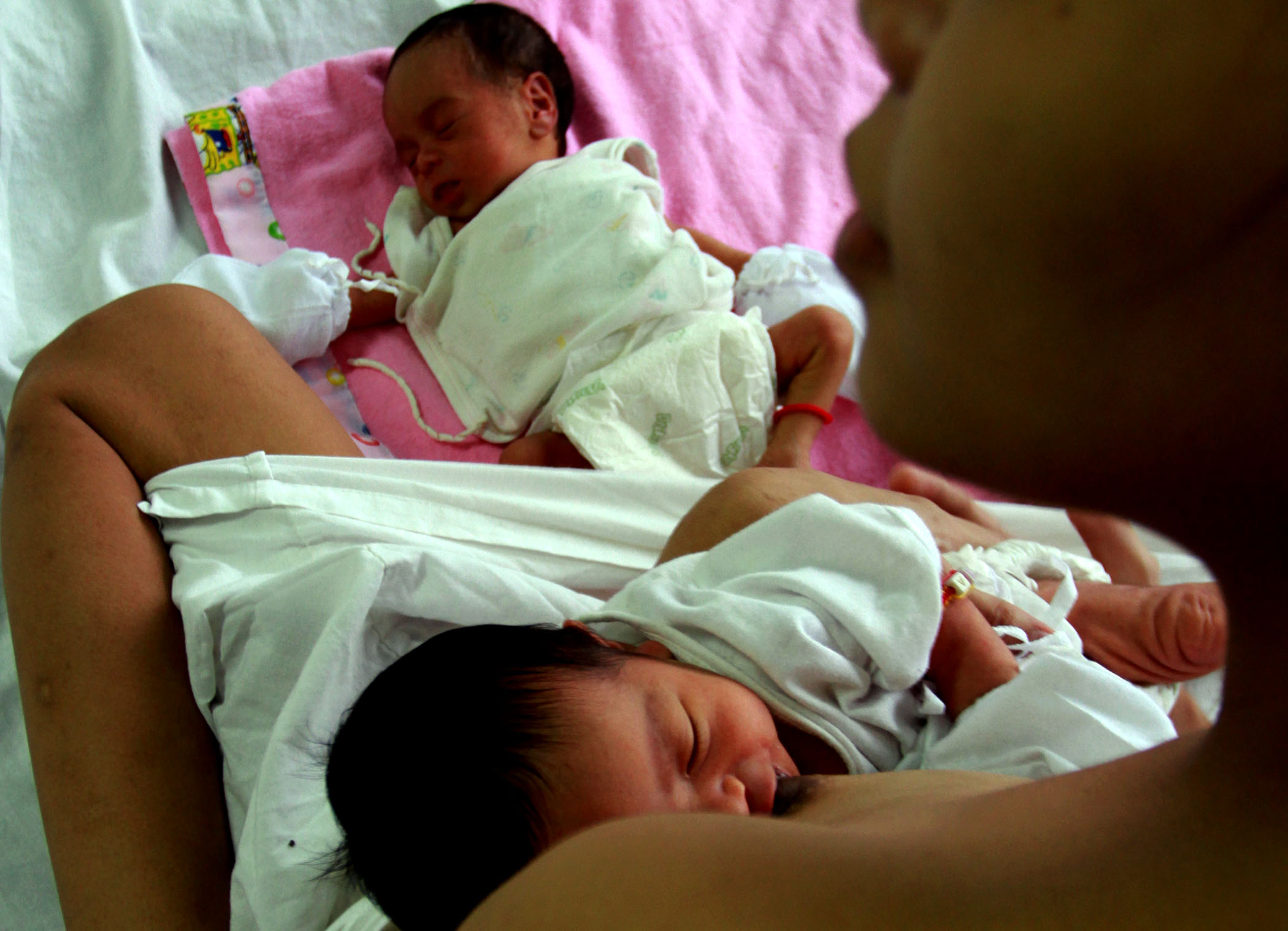 A mother breastfeeds one of her twin babies at Jose Fabella Medical hospital in Manila, Philippines