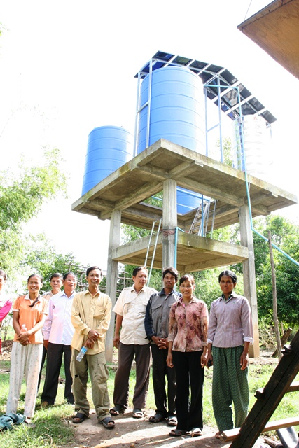 Farmers in front of Bosleav commune's first water user association, posing in front of a solar-powered water pump