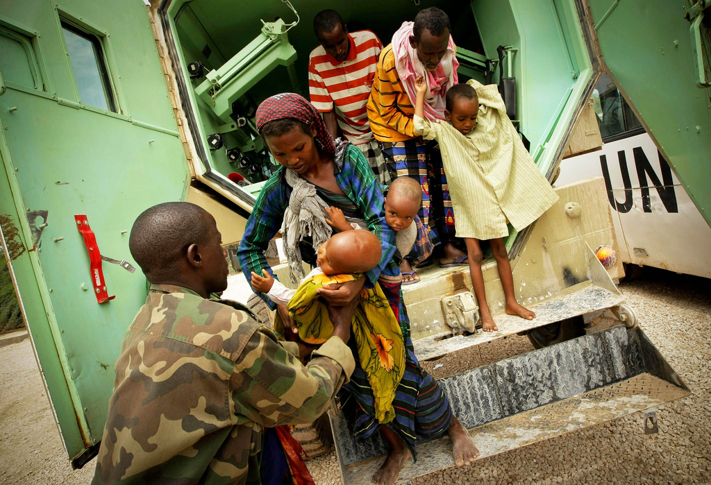 A Somali woman hands her severely malnourished child to a medical officer of the African Union Mission in Somalia (AMISOM), an active regional peacekeeping mission operated by the African Union with the approval of the United Nations