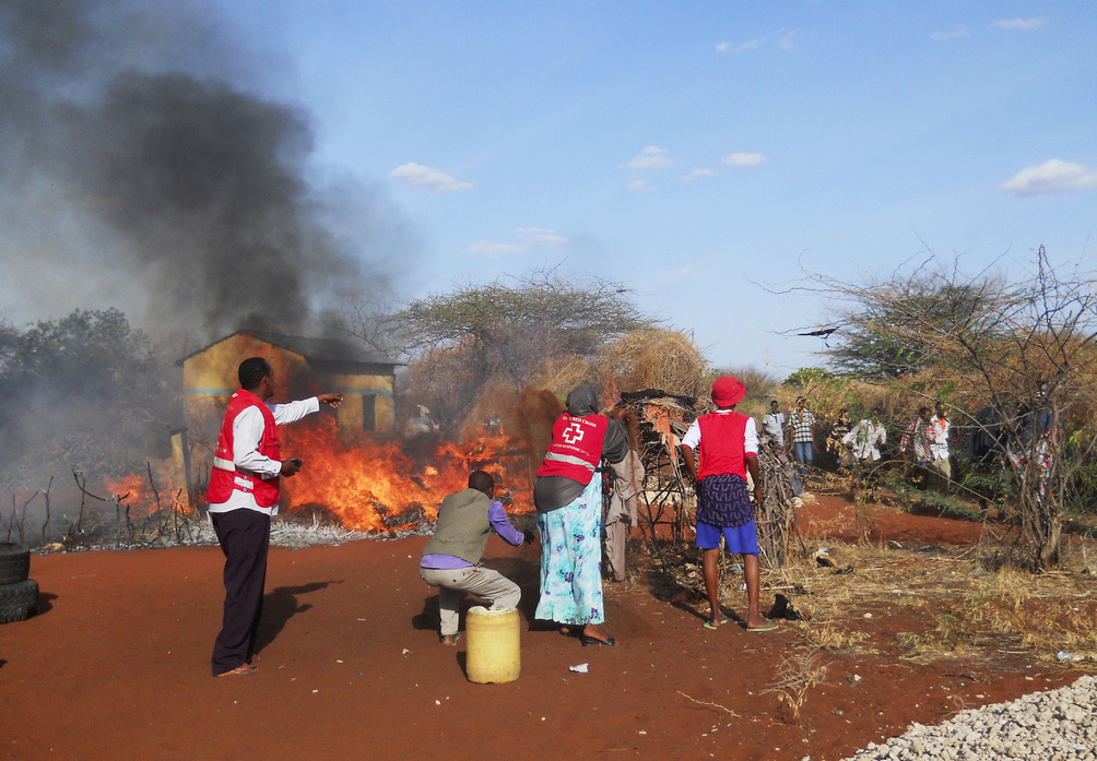 Kenya Red Cross personnel branch helping in demolishing a house to stop fire from spreading in Wajir East