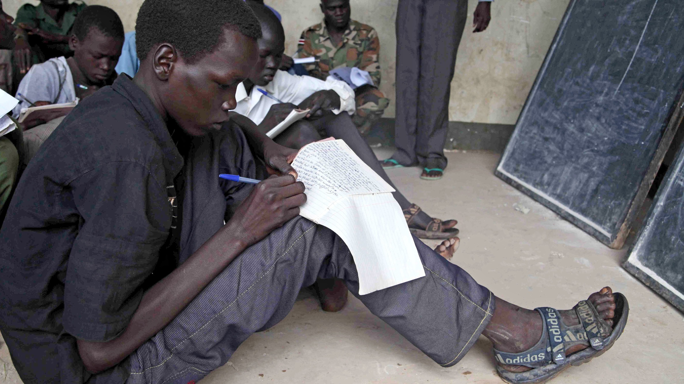 Boy attends English lesson at a military barracks in the Southern Sudanese town of Yei