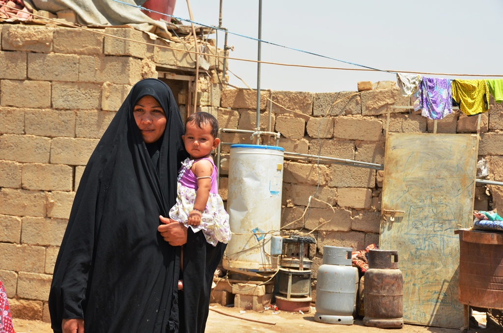 A displaced woman holds her baby at a makeshift settlement, Al-Rustumiiya, on the outskirts of the Iraqi capital Baghdad. Squatters here lack proper electricity, water and sanitation and are at constant risk of eviction