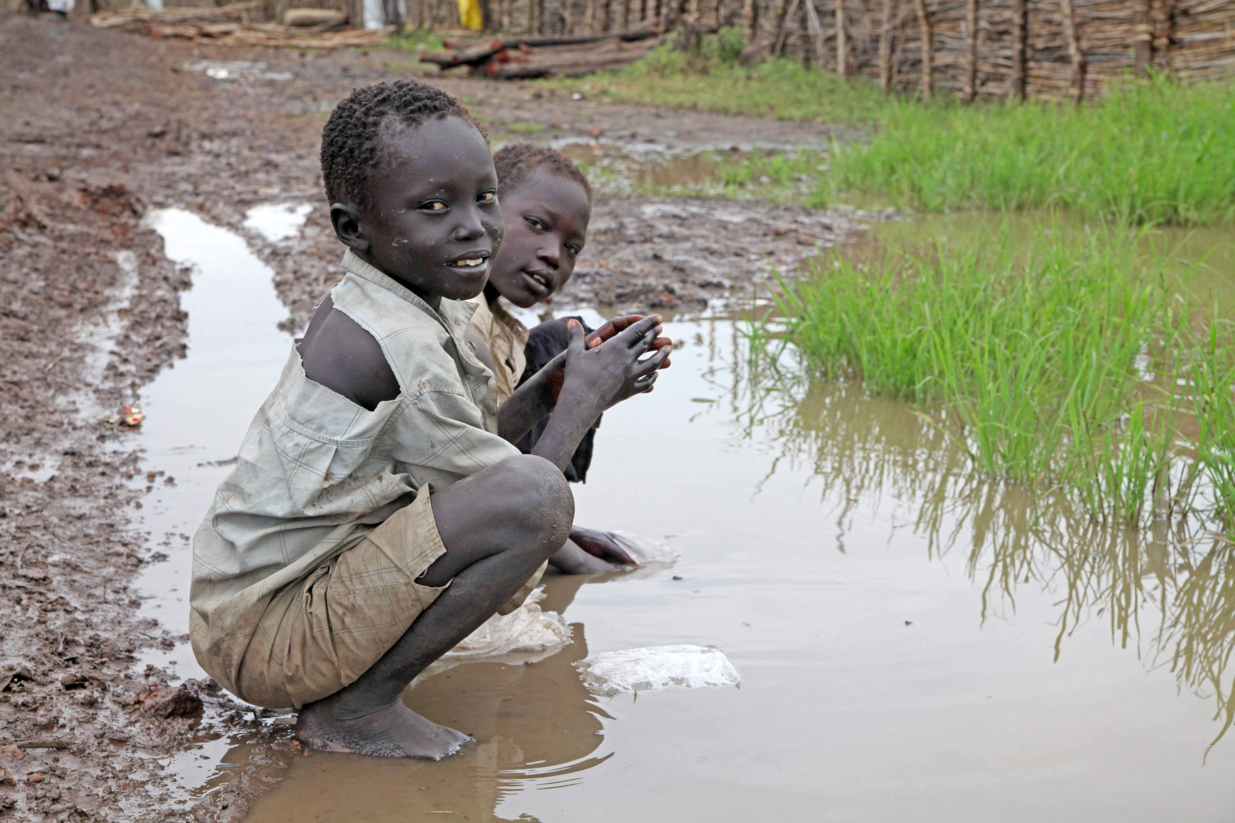 Children at Gendrassa refugee camp in Upper Nile State, South Sudan, play in a dirty puddle. Aid agencies say malnutrition in the camp has declined, but disease is still rife