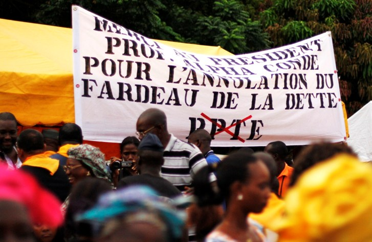 "People at a pro- Alpha Condé rally in the capital Conakry, 29 September 2012. The sign reads: ""Thank you to President Prof. Alpha Condé for the cancellation of the debt burden"