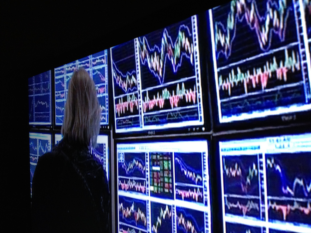 Woman looking at computer screens of stock trades