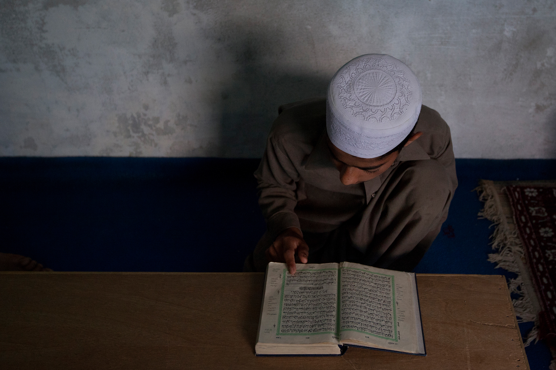 A boy studies the Quran in a religious school in Pakistan
