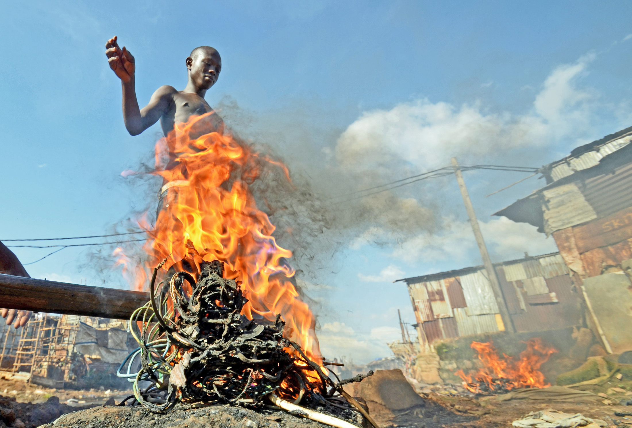 Mohammed Turay burns cables in Freetown's Kroo Bay slum to extract copper which he sells as scrap