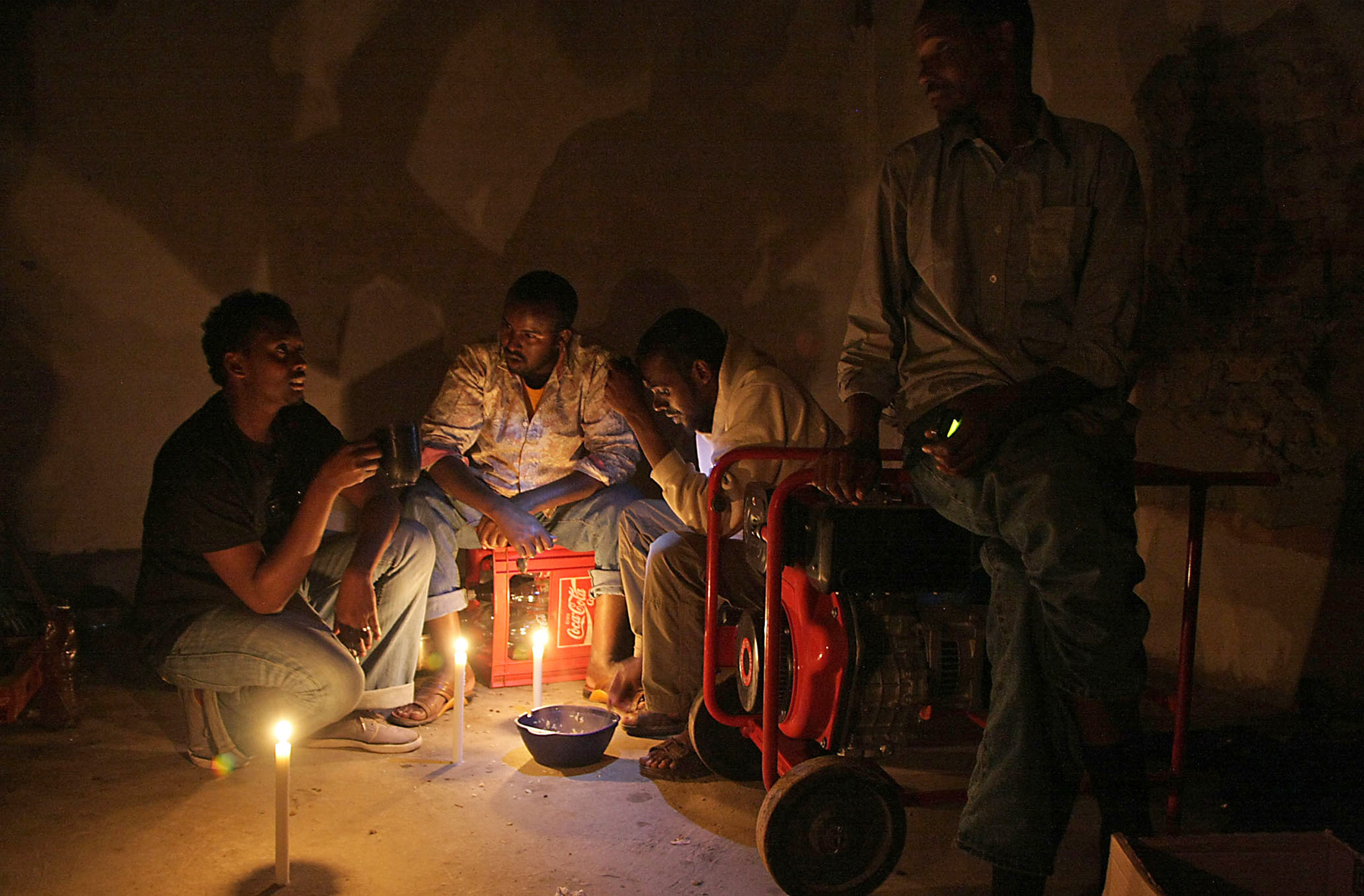 Somali shopkeeper Abdul Abdullah and his three employees share an evening meal in the small living space at the back of the shop
