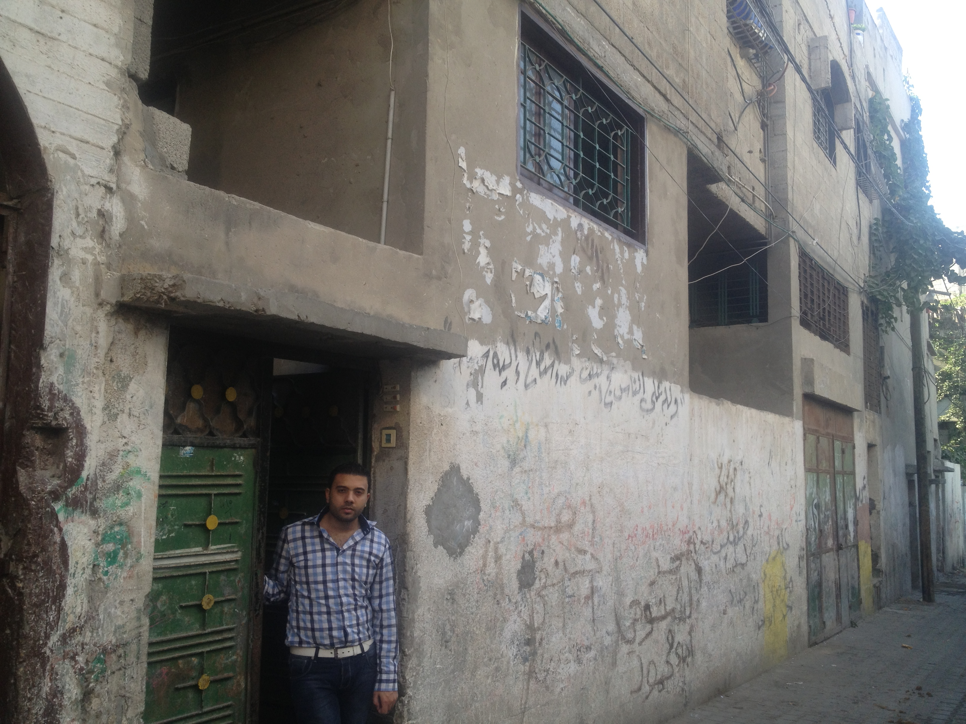 Ayman stand at the front of the house of his parents in Gaza