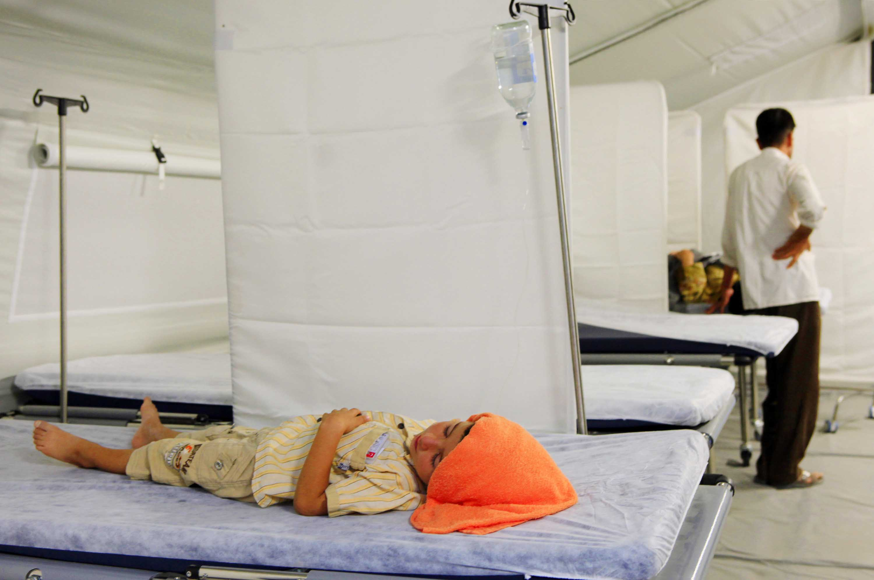 A Syrian child suffering from heat stroke rests in a well-equipped medical centre in the Akcakale refugee camp in southern Turkey, which houses almost 10,000 Syrian refugees. The two most common complaints among refugees visiting the medical centre are he
