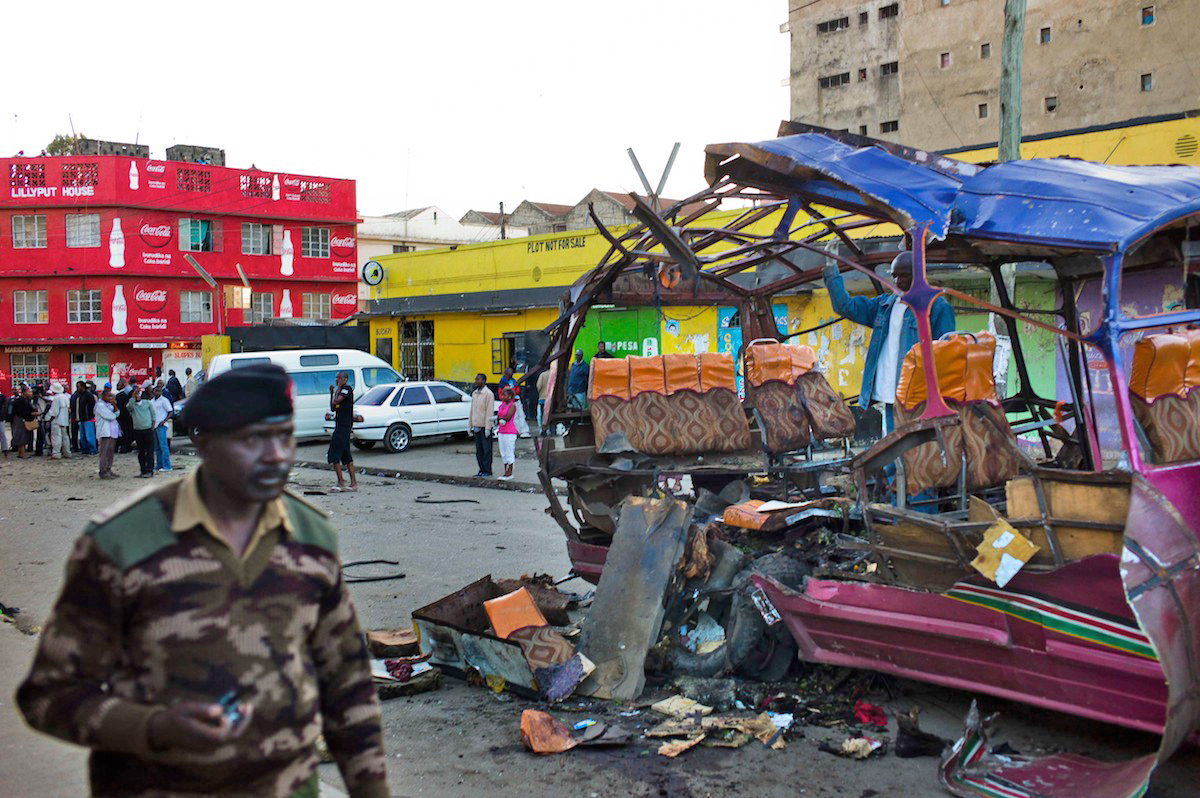 A policeman walks past the remains of a public minibus blown up in the Eastleigh district of Nairobi on 18 November