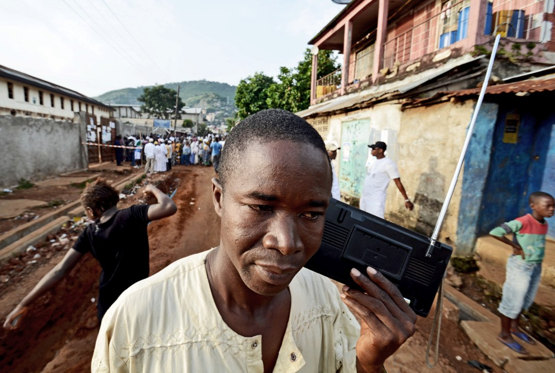 A man listens to the radio as people wait to vote in legislative and presidential elections 17 November 2012 in  Fourah Bay, Freetown