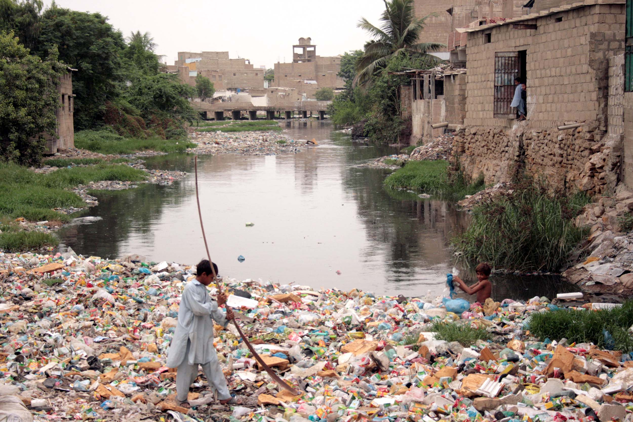 A boy passes through the heap of garbage in western Karachi as municipal company has not been able to collect the garbage from the area
