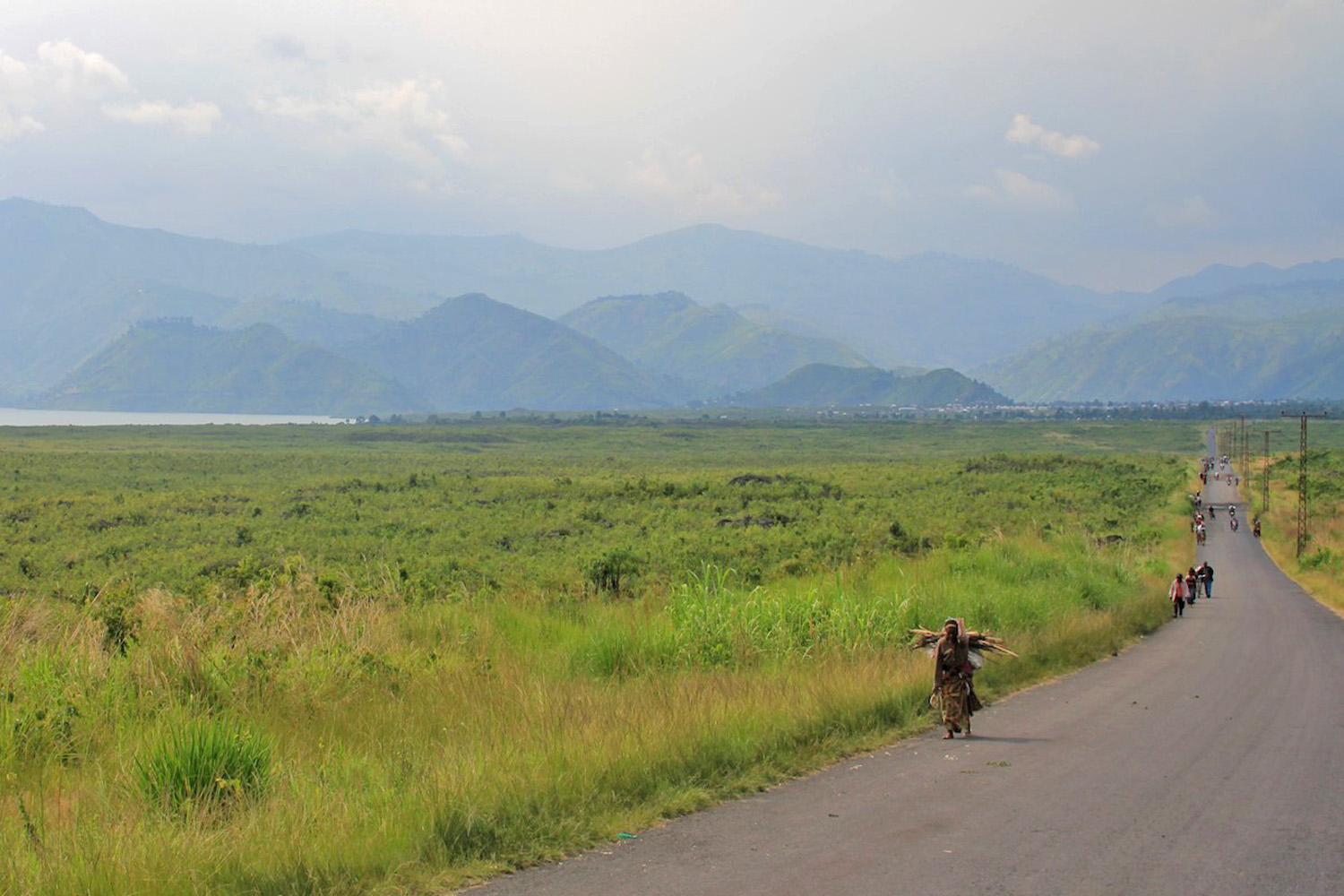 Men and women walk towards Goma from Sake, where residents still report hearing fighting in the hills around