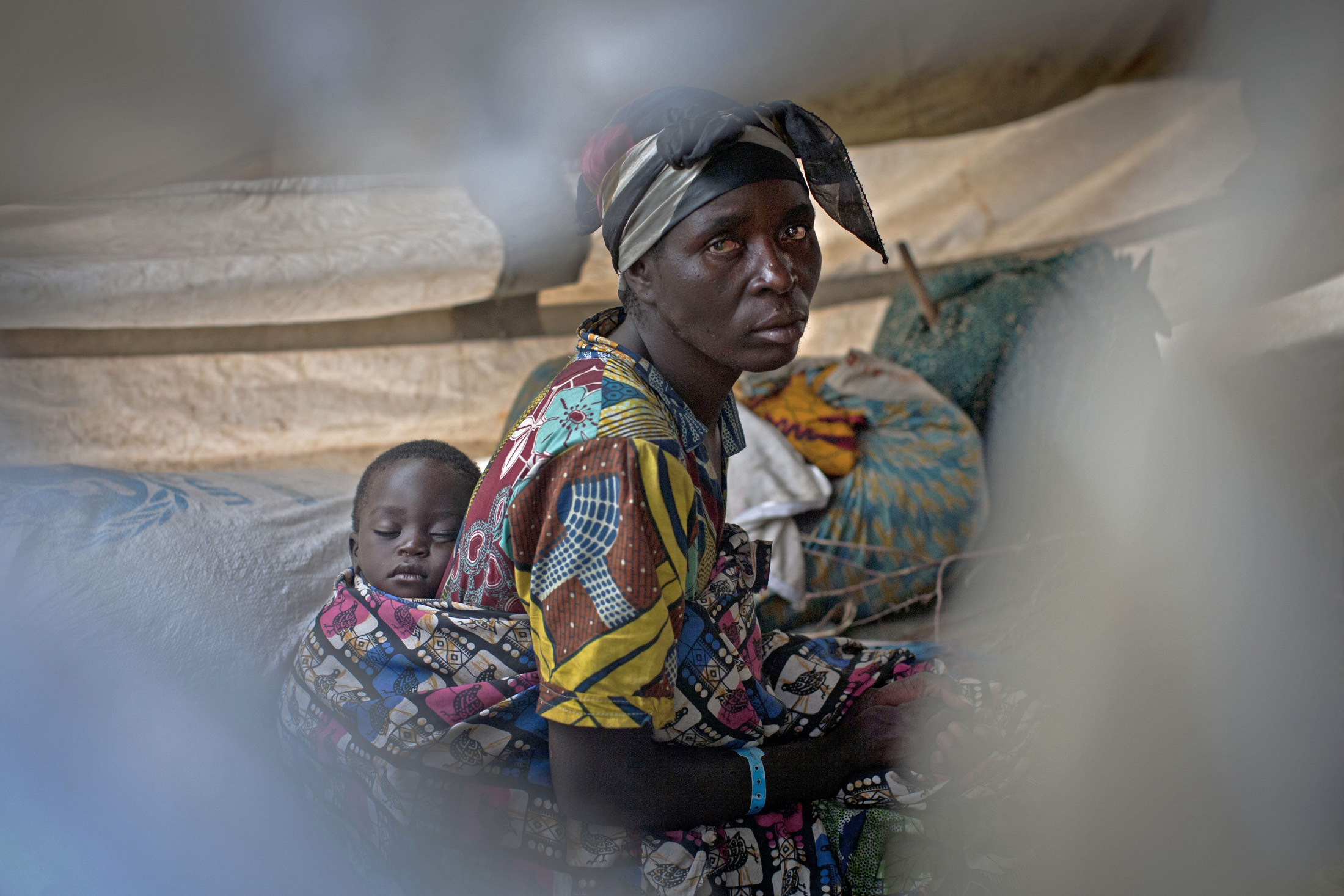 A woman and her baby take shelter at Don Bosco Orphanage in Goma, Democratic Republic of Congo. They have arrived from the town of Sake, where M23 rebels are fighting government troops. [November 2012]
