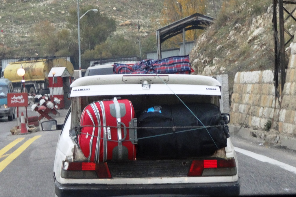 A car with a Syrian license plate crosses the border from Syria to Lebanon in the midst of an ever-worsening civil war
