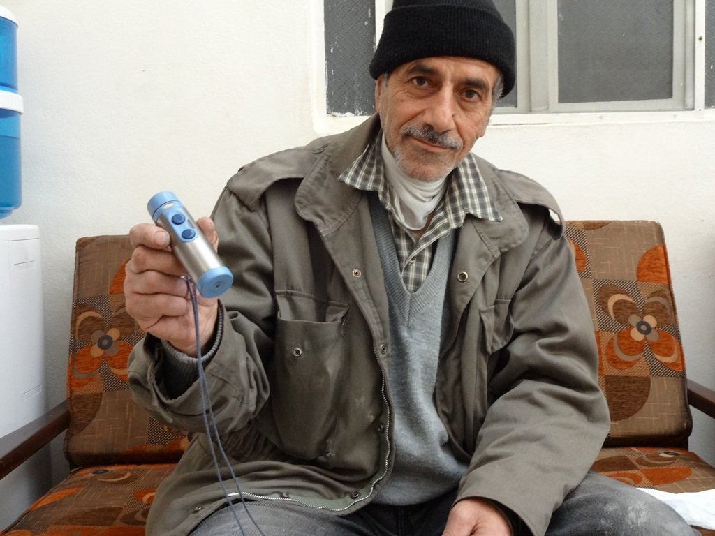Eid Hanani uses this machine to help him speak after removing a cancerous tumour from his throat four years ago. Now, he has discovered a new cancer in his bladder, and the injections he needs for treatment are no longer available in Syria because of the