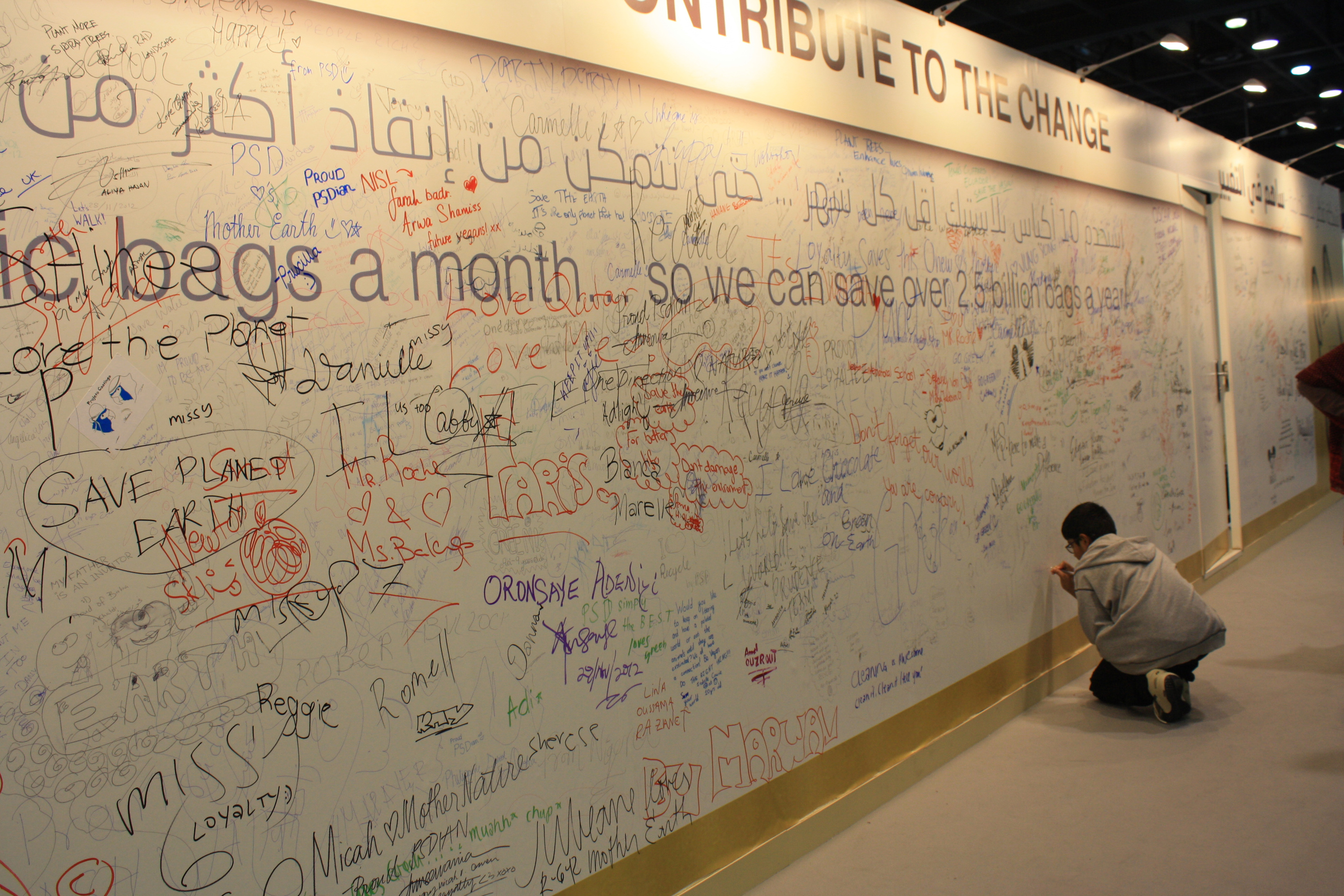 A young boy signs a message to save the planet at the Qatar Sustainability Expo organised to run concurrently with the climate change talks and create awareness