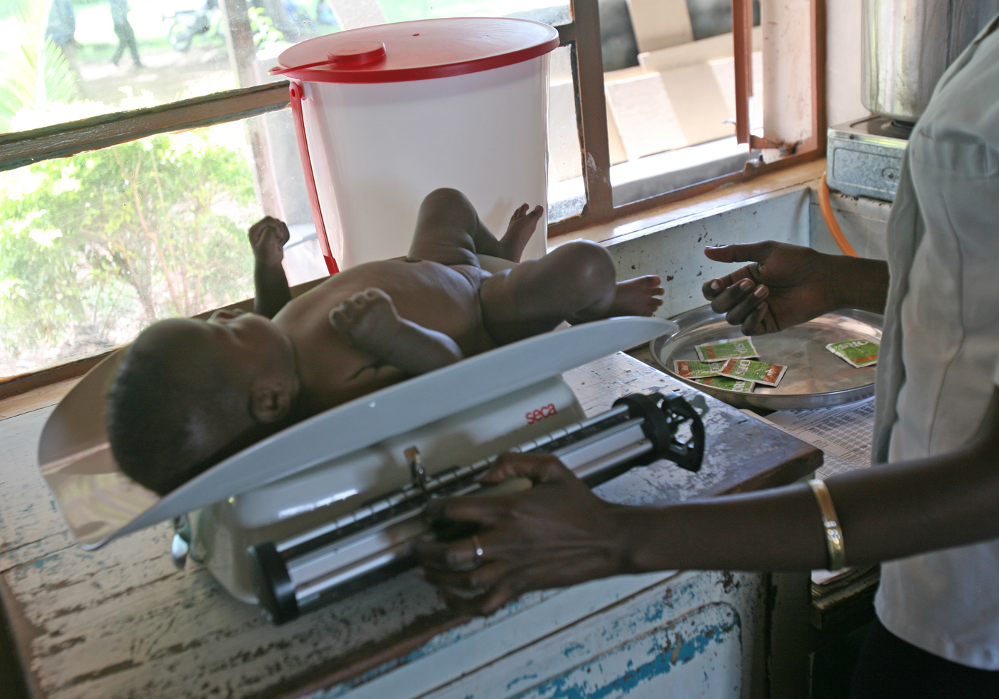 A nurse takes a child's weight at a hospital in western Kenya