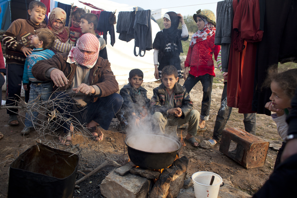 Tomato and potato soup being cooked on an open fire at Qah Camp for displaced Syrians. The nearly 4,000 displaced people living at Qah Camp lack electricity or stoves. With the arrival of winter, the situation has become desperate. Camp officials say they