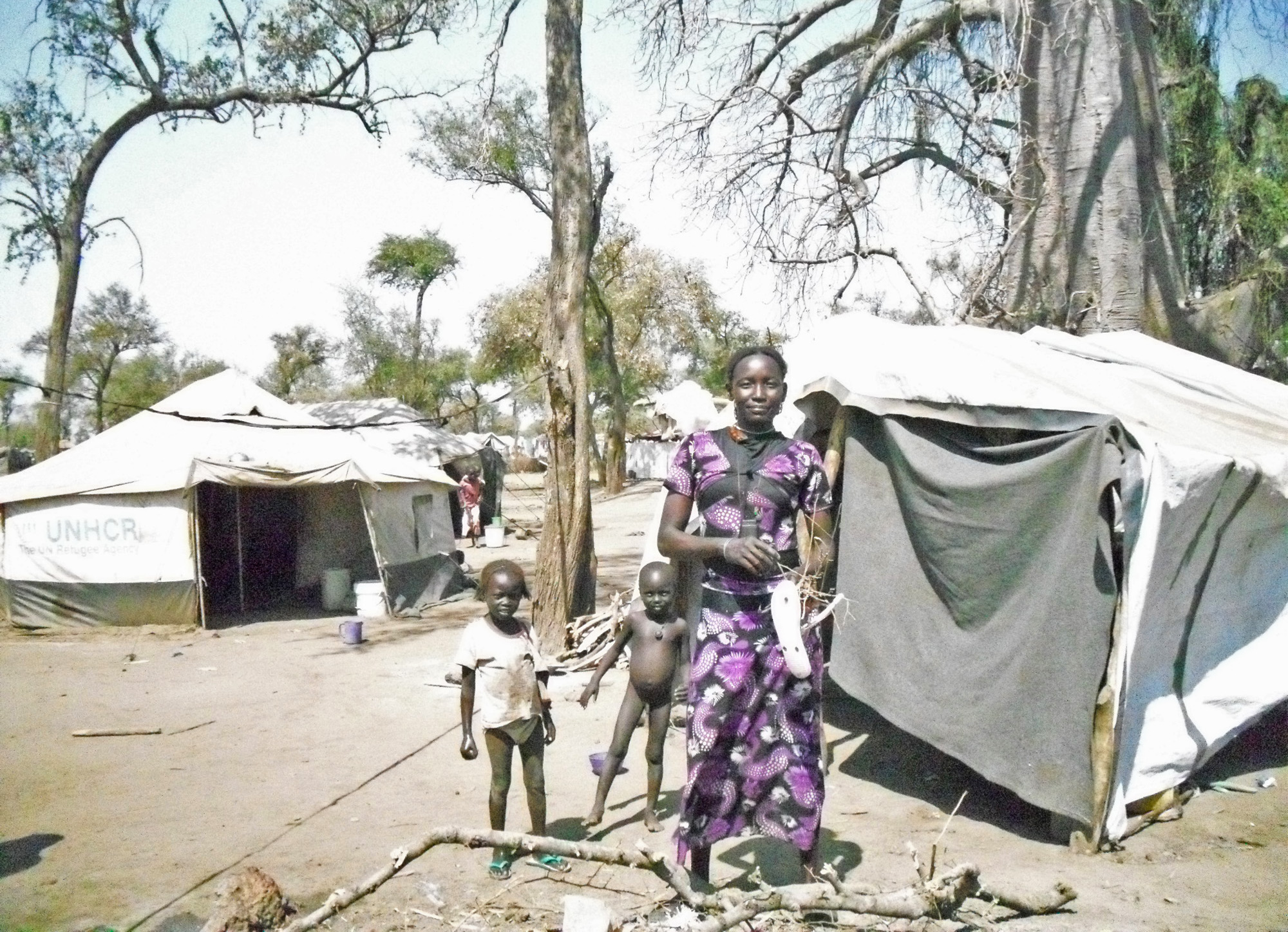 A woman with her children outside their home in Batil camp