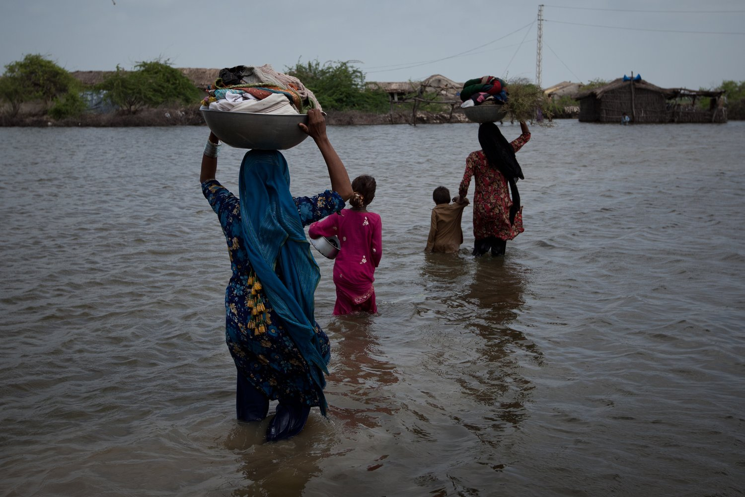 Residents carry their belongings back to their flooded village in the Badin district of Pakistan's Sindh province, on September 14, 2011
