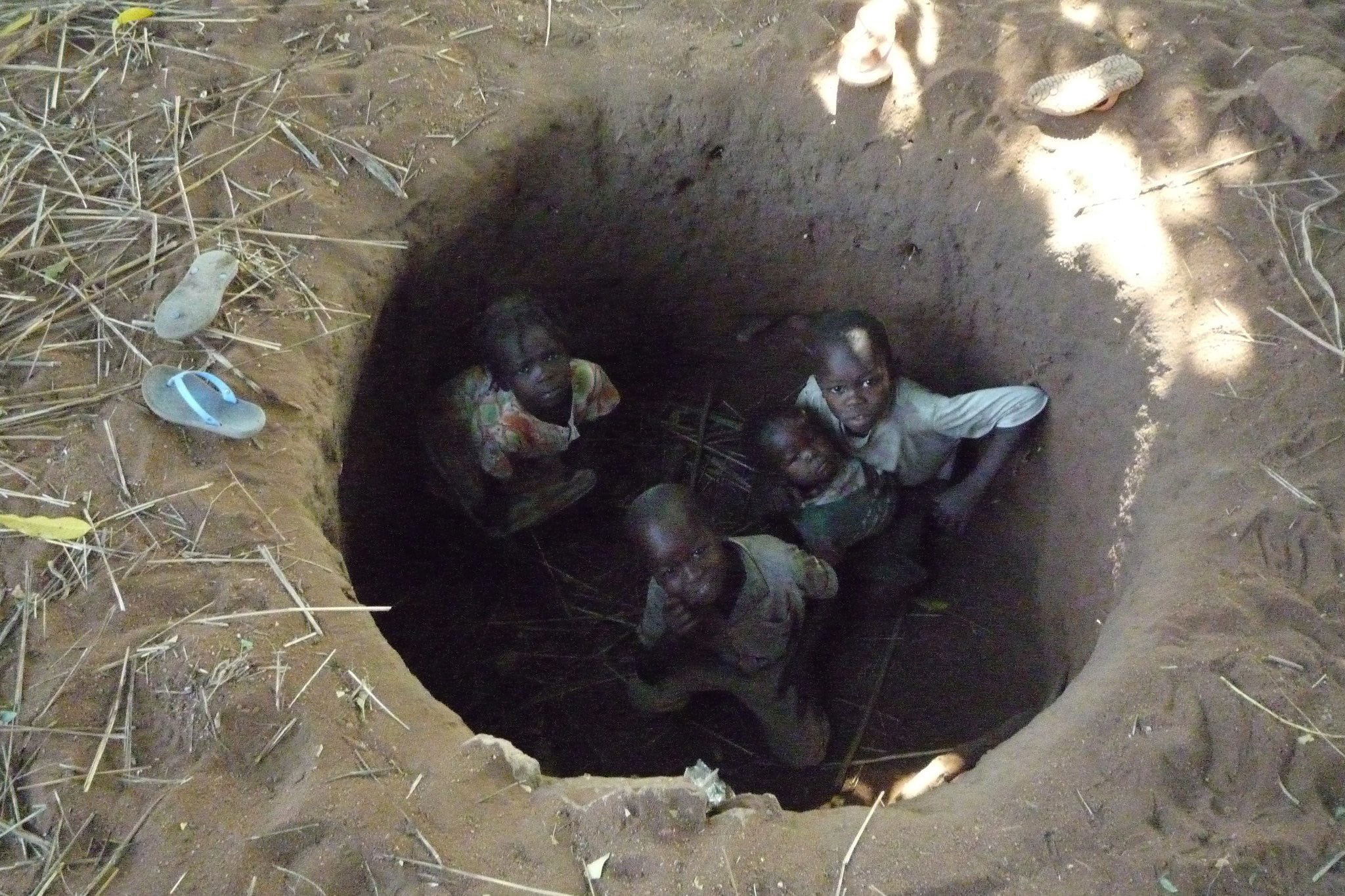 Nuba children shelter in a foxhole at the first sound of an Antonov bomber passing overhead