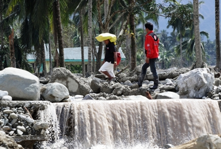 Farmers return to their farming village in the town of New Bataan in the southern Philippines that was devastated by Typhoon Bopha in December 2012