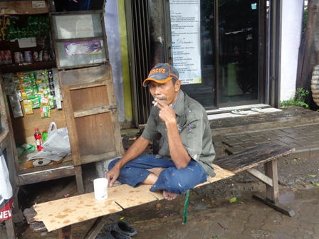 A man enjoys a cigarette on the streets of Jakarta