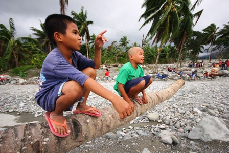 Two boys survey the damage in Mindanao's Compostela Valley in the wake of Typhoon Bopha which struck the area on 4 December 2012. Some 6.2 million people were affected