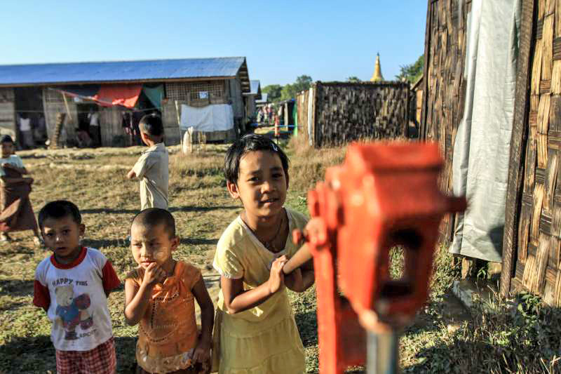 IDP children play at a water pump in Jyenaysu ward near Sittwe, capital of Myanmar's Rakhine state