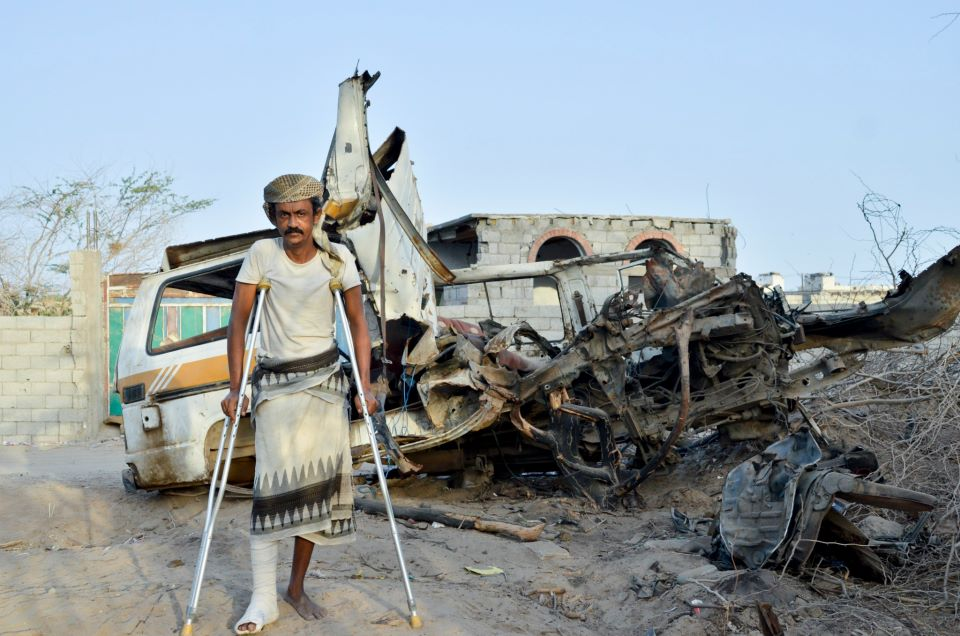 Ali Naser Awaas stands in front of his bus that blew up when he drove over a landmine infront of his house in Zinjibar, Abyan as he was beginning his work soon after he returned in October 2012. Ali lost his son and injured his leg in the accident. His on