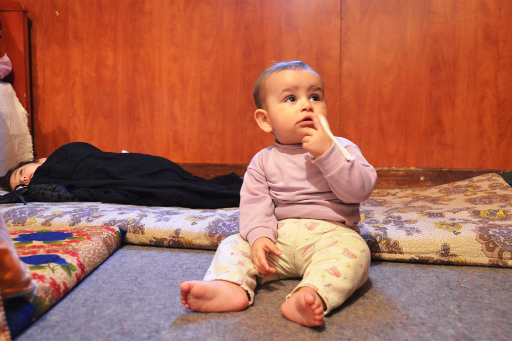 A 9-month old baby from Rural Damascus, Syria, sits on the floor of a room where his family has sought refuge in Tyre, South Lebanon, next to his cousin, sleeping on the floor