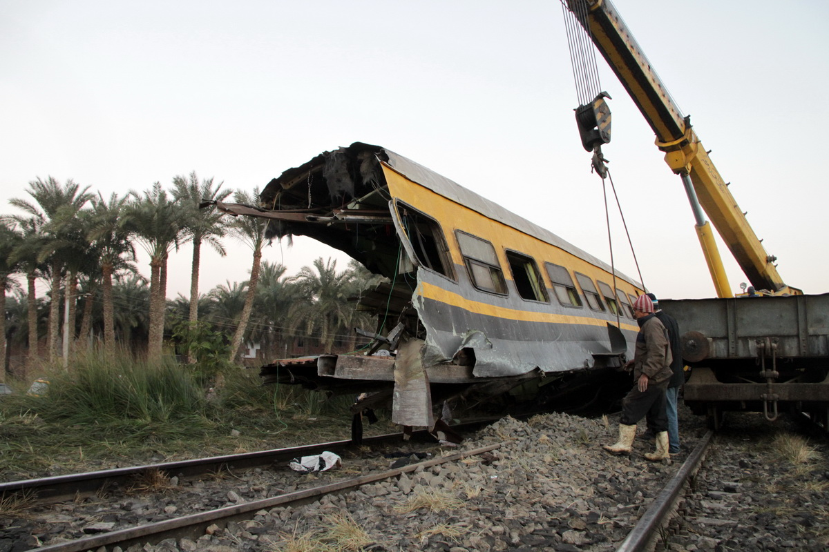 Workers try to remove the wreckage of a train carriage that derailed south of Cairo on January 14 2013, killing 19 people and injuring tens of others