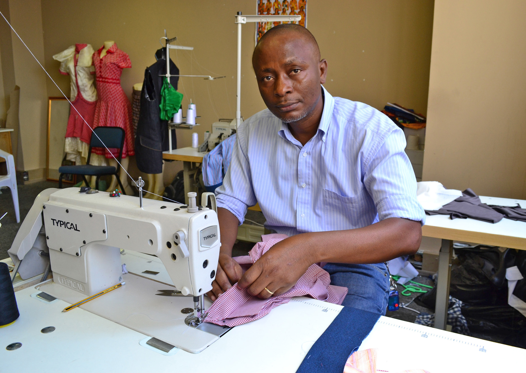 With business skills training and a grant from Jesuit Refugee Service, Clement Mukengeshay, a refugee from the Democratic Republic of Congo, has started a dressmaking business in inner-city Johannesburg