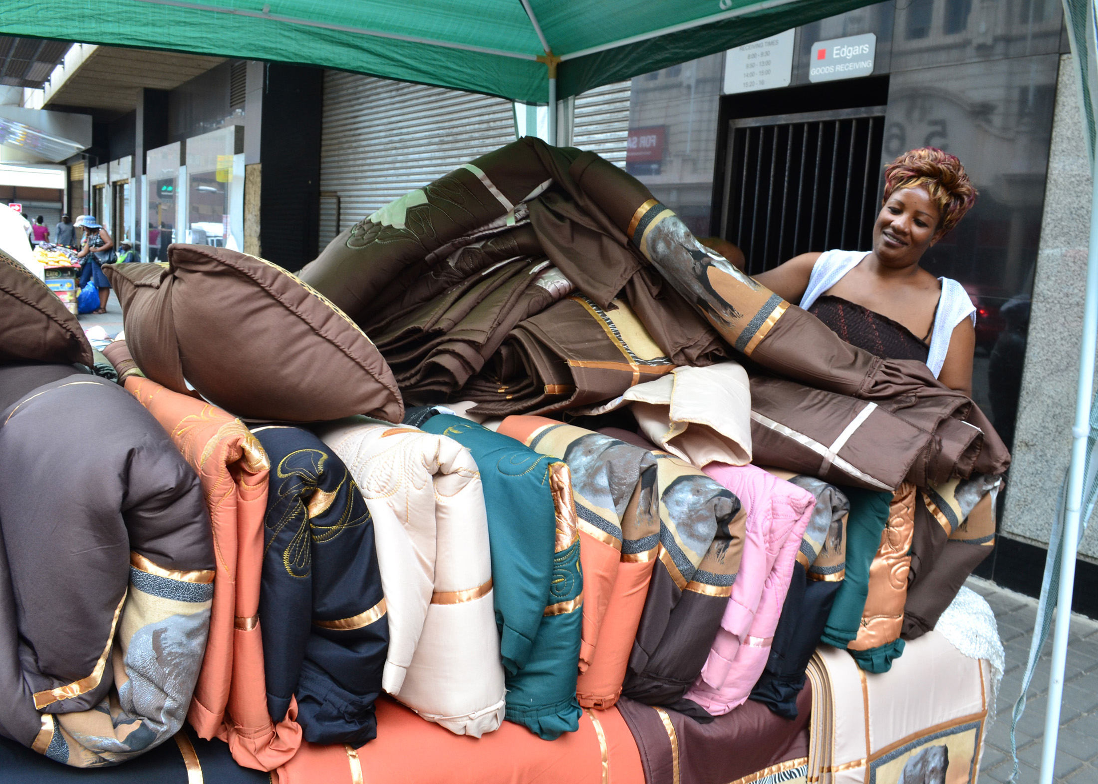 Anesu Sithole, from Zimbabwe, has been making and selling bedspreads and cushions from a stall in inner-city Johannesburg for four years. Without access to  training or capital she cannot expand the business and earns just enough to feed her family