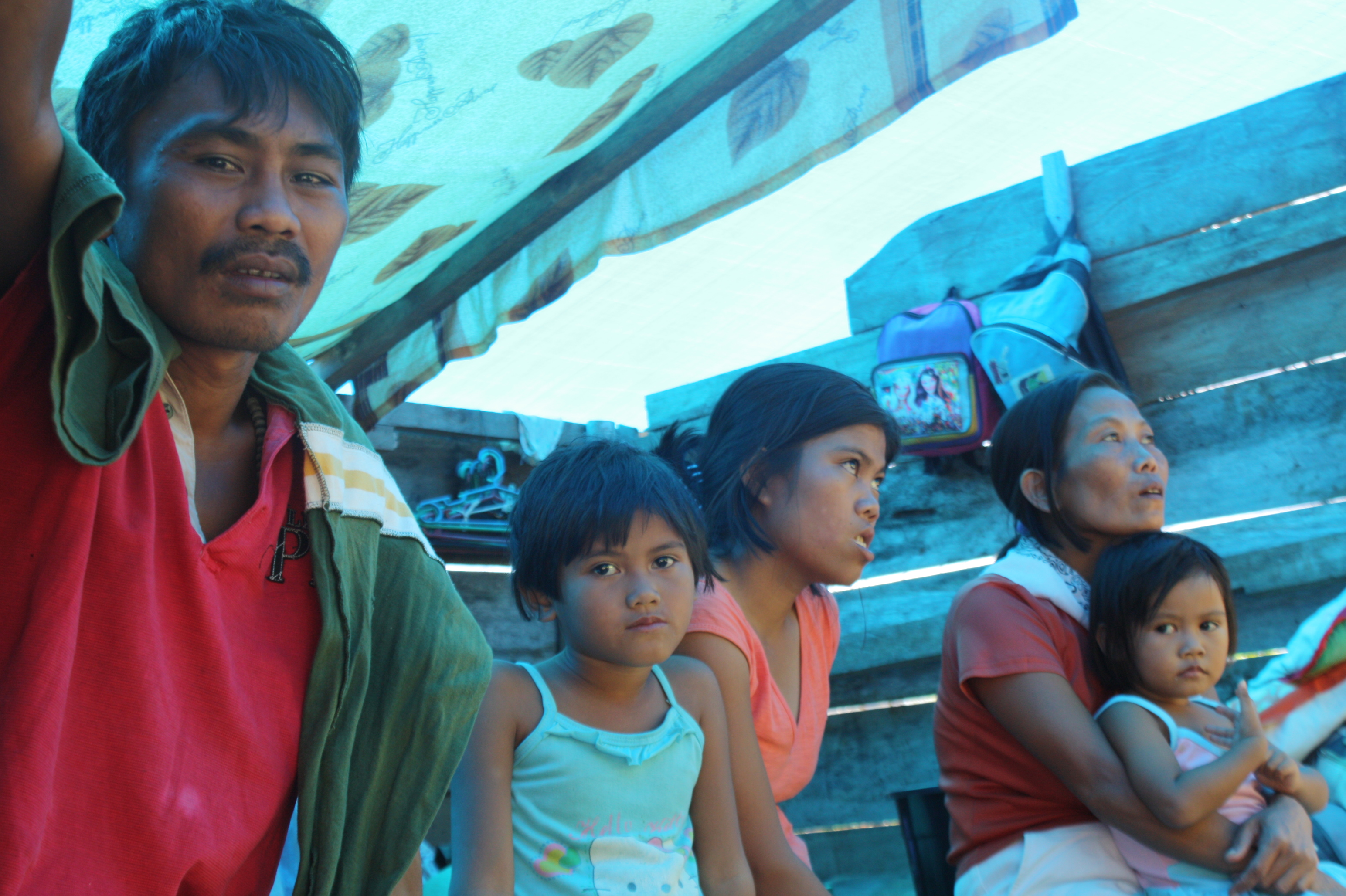 Families in Panansalan, a barangay hit by Typhoon Bopha/Pablo on 4 December 2012, continue living in their damaged home two months afterward