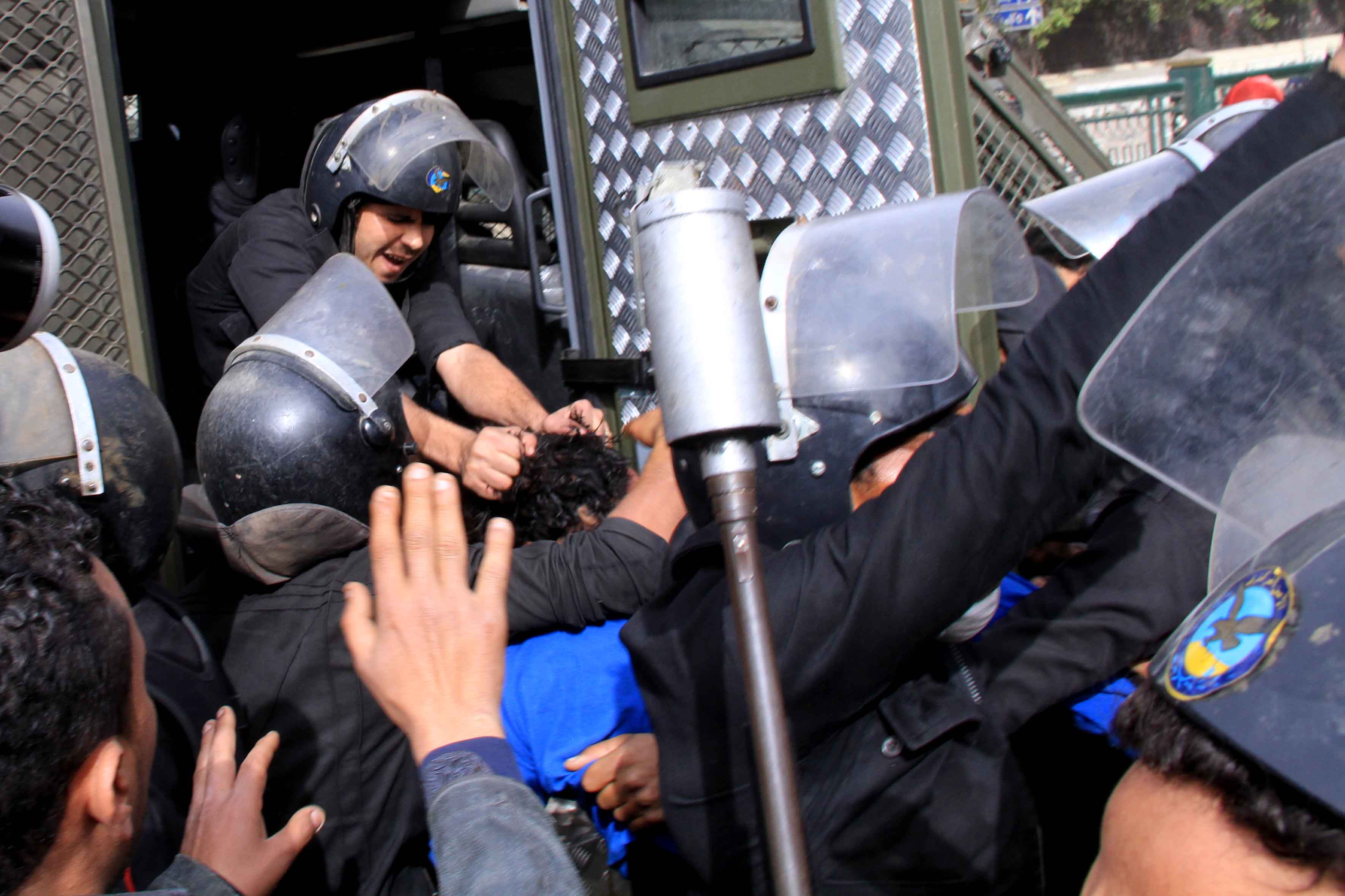 On the second anniversary of the 2011 revolution, policemen in Egypt pull one protestor by the hair after arresting him in central Cairo, the scene of violent clashes between policemen guarding state institutions and hotels and protestors