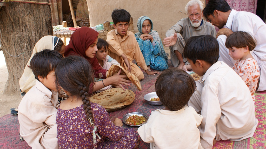 An IDP family living in a host community in Charsadda District, in the Pakhtunkhwa province of Pakistan, has lunch. The elder of the family just picked up their one-month ration from a WFP distribution point