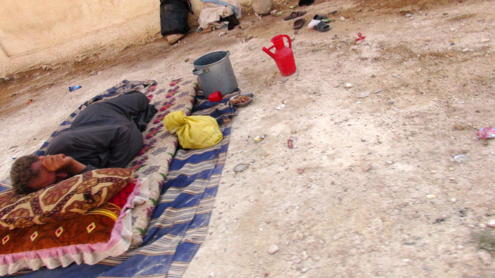 A displaced man sleeps in Syria. Many communal shelters are poorly equipped, lacking furniture and access to basic hygiene