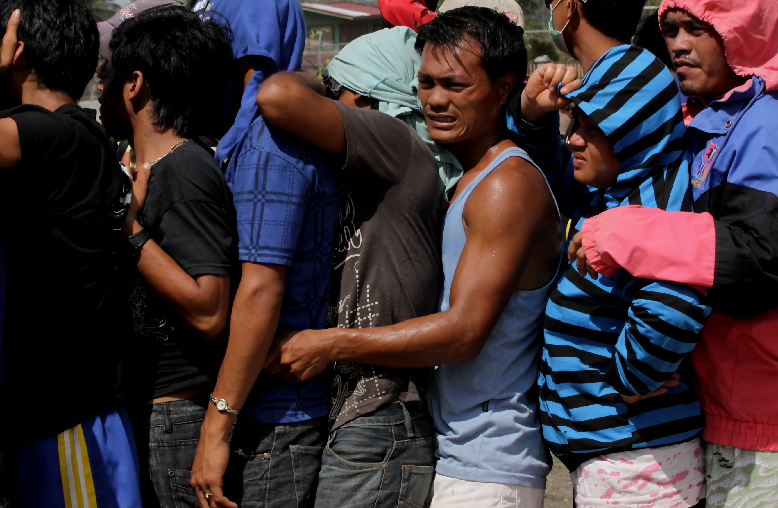 Compostela Valley, Philippines - Men crowd each other as they queue for food relief in a southern Philippine ravaged by typhoon Bopha