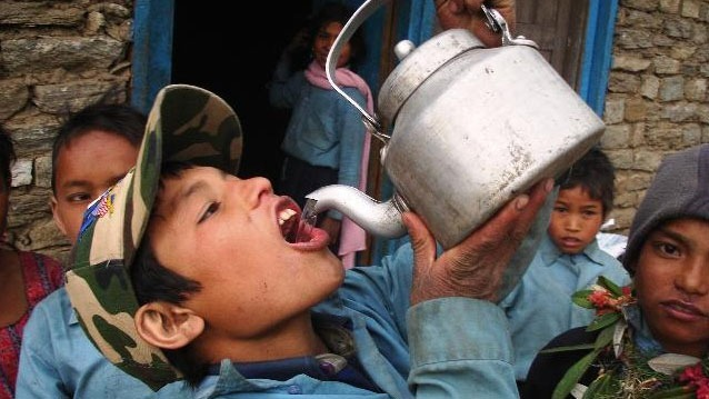 A young boys sips water from a teapot outside Jumla. The Karnali region is the poorest and least developed area of the country